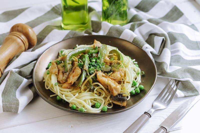 Spaghetti avec du blanc de poulet grillé et paprika vert, pois et oignon vert photo libre de droits