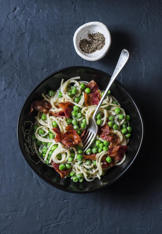 Spaghetti with bacon and creamy green peas on a dark background stock image