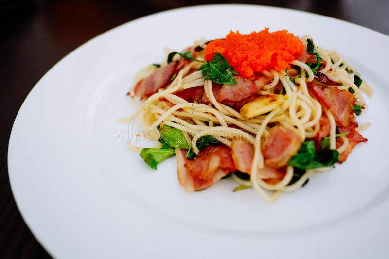 Spaghetti. Bacon and tobiko Spaghetti on white dish royalty free stock images