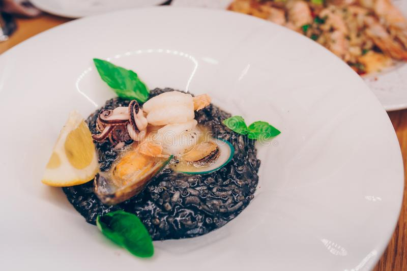 Spaghetti black rice with seafood in sause with lemon slice. spaghetti with scallops shells squid ink with prawns, mussels and par royalty free stock photography
