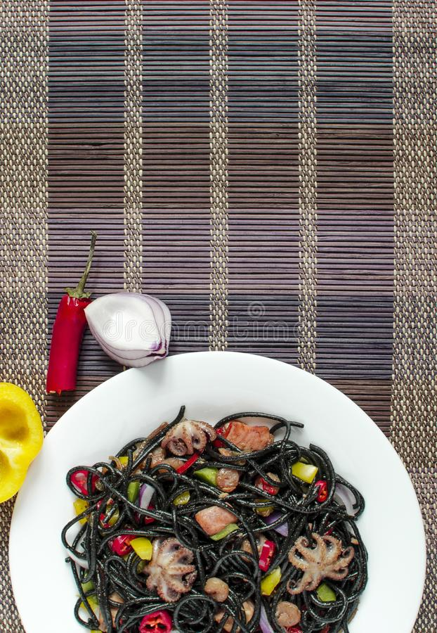 Spaghetti black with seafood and vegetables on a white plate multi-colored background top view vertical. Spaghetti black with seafood and vegetables on a white stock images