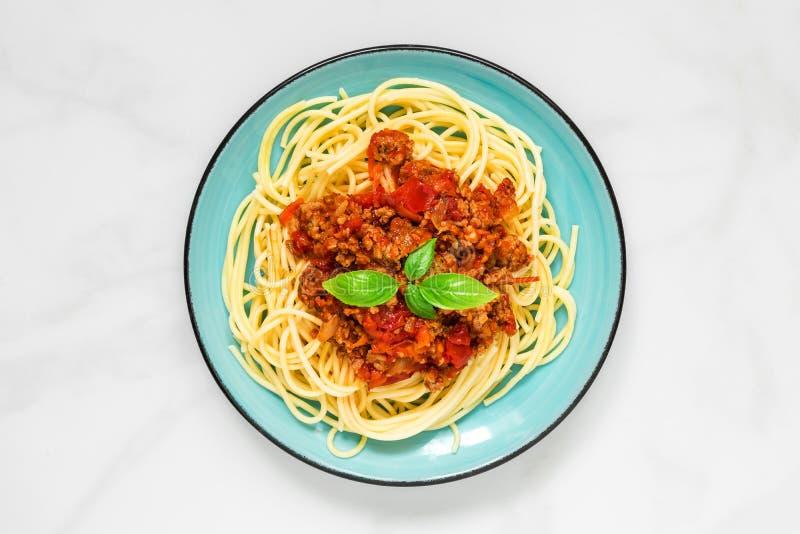 Spaghetti bolognese op een blauwe plaat op witte marmeren lijst Gezond voedsel Hoogste mening royalty-vrije stock afbeeldingen