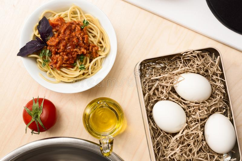 Spaghetti bolognese, tomato, olive oil and organic eggs on beige. Table above view stock images