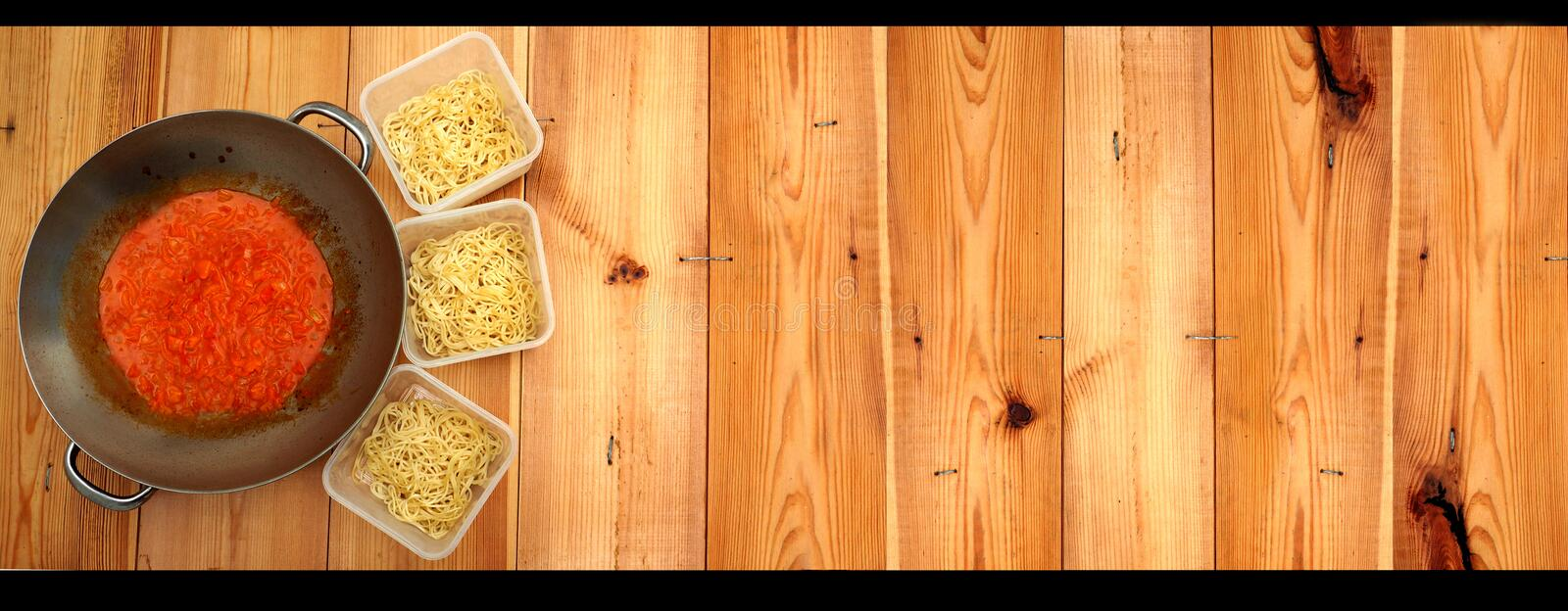 Spaghetti in box and sauce in pan on background wood. I`m cooking to frying a spaghetti sauce in stainless steel pan and spaghetti in three plastic boxes, Design stock images