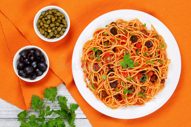Spaghetti with capers. olives, anchovies, tomato sauce. Delicious Spaghetti alla puttanesca with capers, olives, anchovies, tomato sauce sprinkled with parsley royalty free stock photos