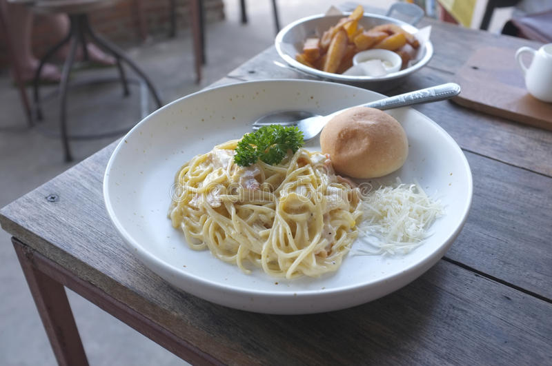 Spaghetti Carbonara with bun and French fries stock photography