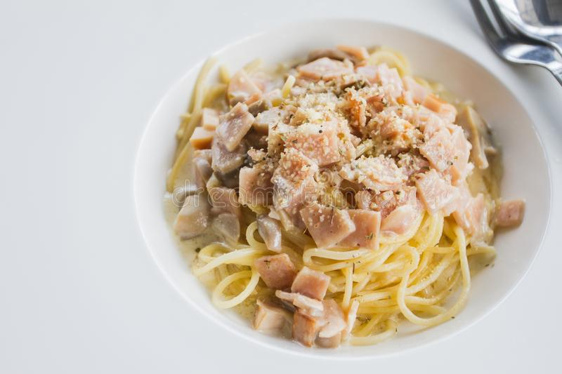 The spaghetti carbonara with cream cheese and ham on the table ready to be served. royalty free stock photos