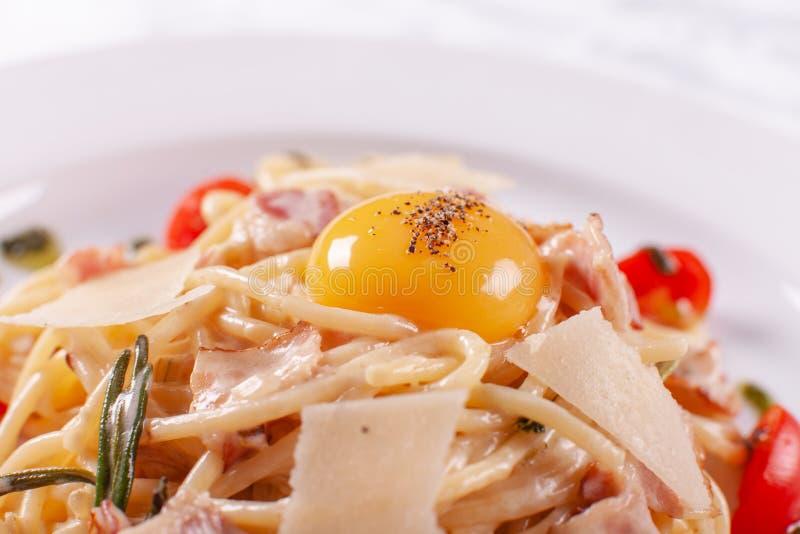 Spaghetti Carbonara Italiaanse Deegwaren op witte plaat met parmezaanse kaas, ham en dooier stock afbeelding