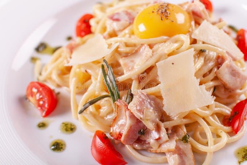 Spaghetti Carbonara Włoski makaron na bielu talerzu z parmesan, baleronem i yolk, fotografia stock