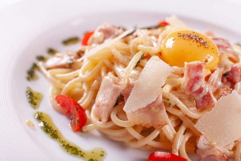 Spaghetti Carbonara Włoski makaron na bielu talerzu z parmesan, baleronem i yolk, obrazy stock