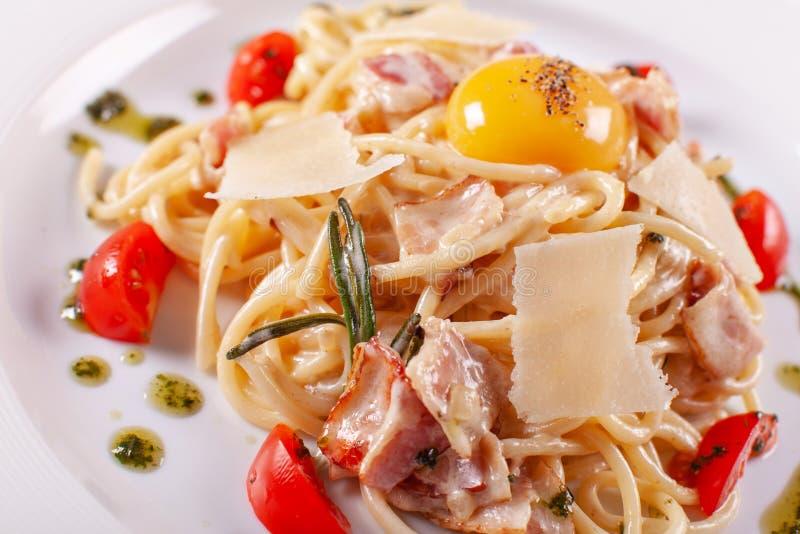 Spaghetti Carbonara Włoski makaron na bielu talerzu z parmesan, baleronem i yolk, fotografia royalty free
