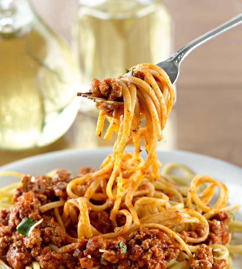 Spaghetti che appendono su una forcella al pranzo immagini stock