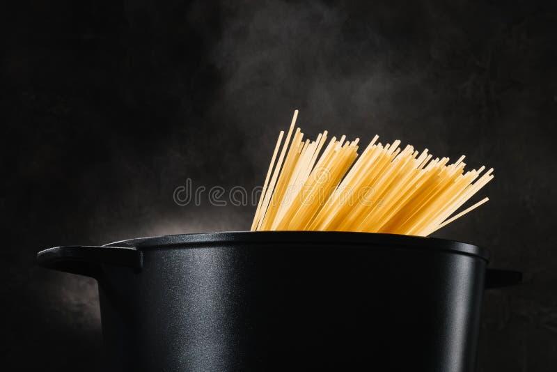 spaghetti che bollono in pentola nera fotografia stock