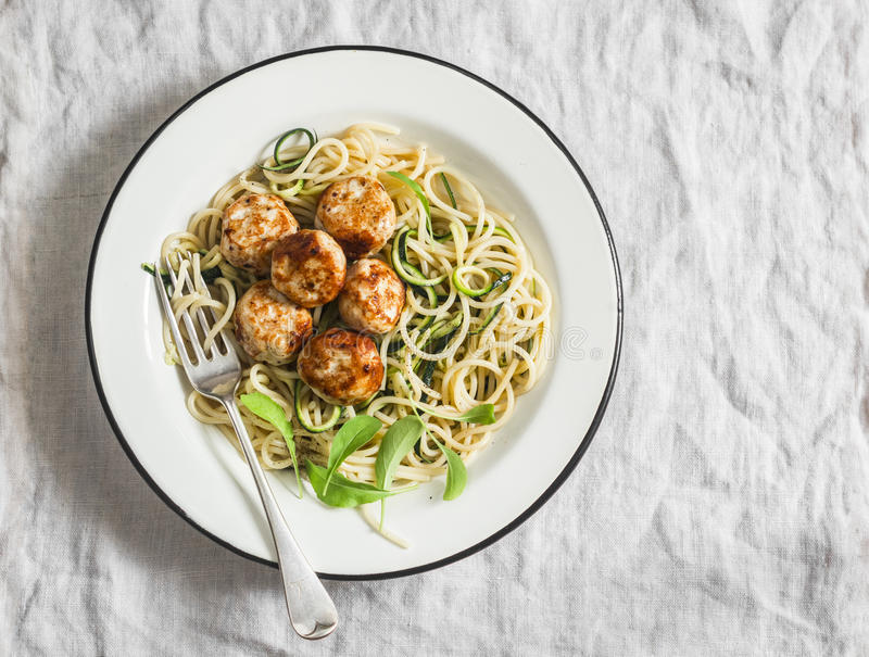 Spaghetti with cheesy chicken meatballs and zucchini noodles. Delicious lunch on a light background royalty free stock images