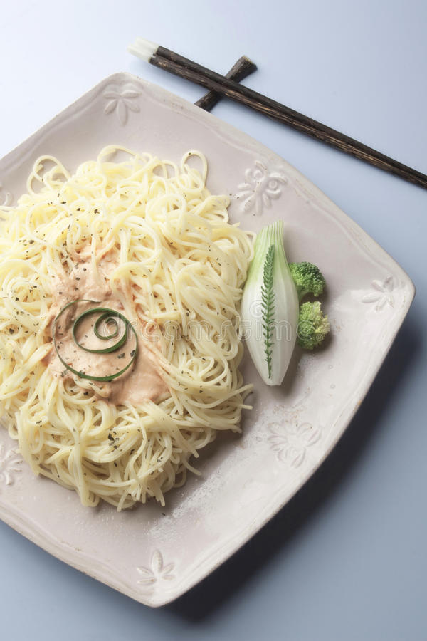 Spaghetti with chop sticks. And vegetables served in a plate stock photo