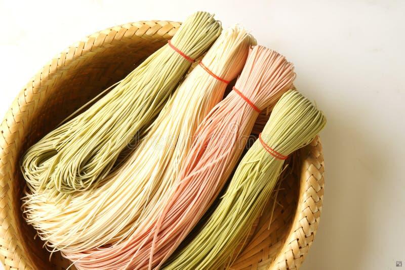 Spaghetti cinesi variopinti sul canestro di bambù nel fondo bianco fotografie stock