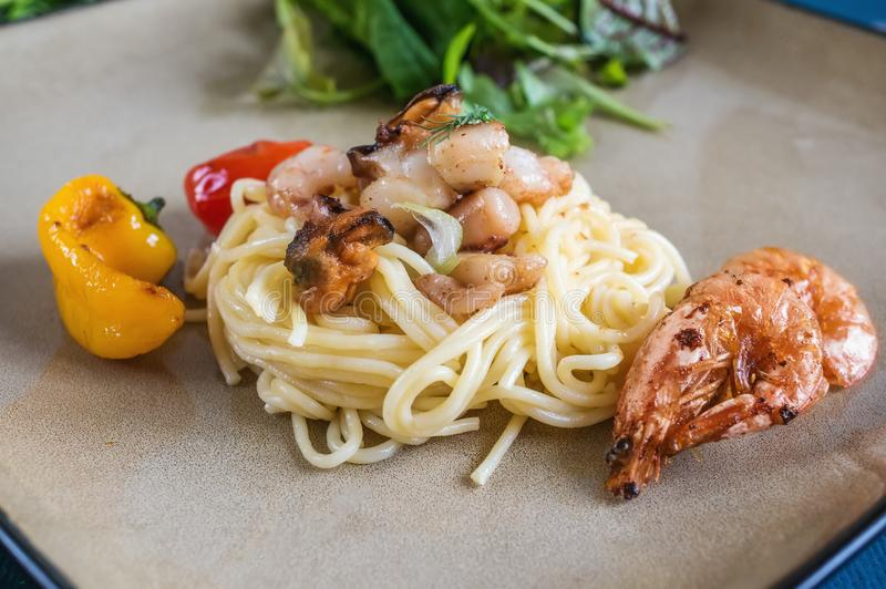 Spaghetti with clams shrimp scallops and various seafood on a ceramic plate close-up royalty free stock photo