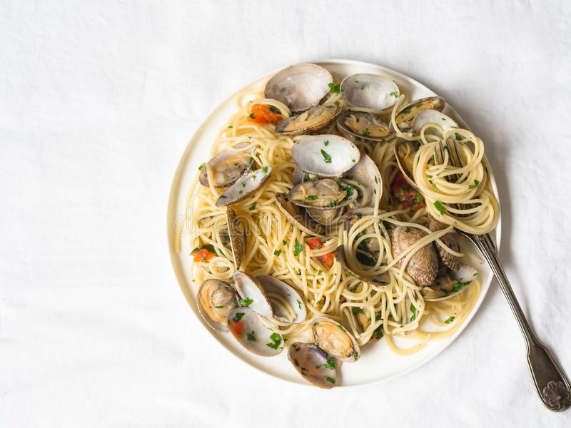 Spaghetti with clams, tomatoes, garlic and parsley on a white plate and rustic fork on a white background. Top view. Spaghetti with clams, tomatoes, garlic and stock images