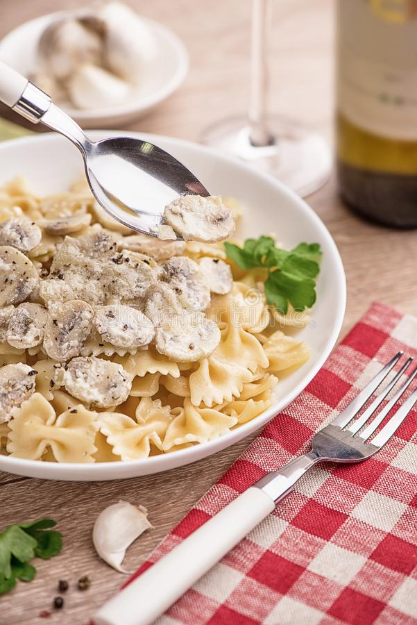 Spaghetti con i funghi prataioli ed il prezzemolo su una tavola di legno leggera in un ristorante immagini stock