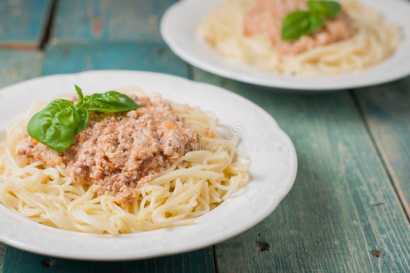 Spaghetti con la salsa della carne su fondo blu fotografia stock