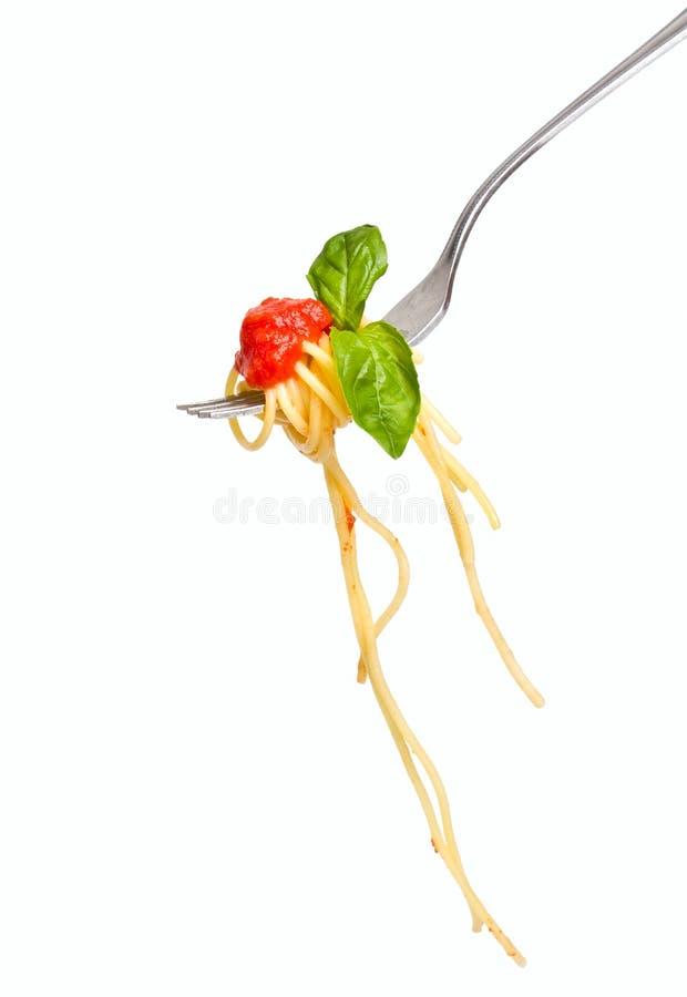 Spaghetti con salsa e basilico sulla forcella immagini stock libere da diritti