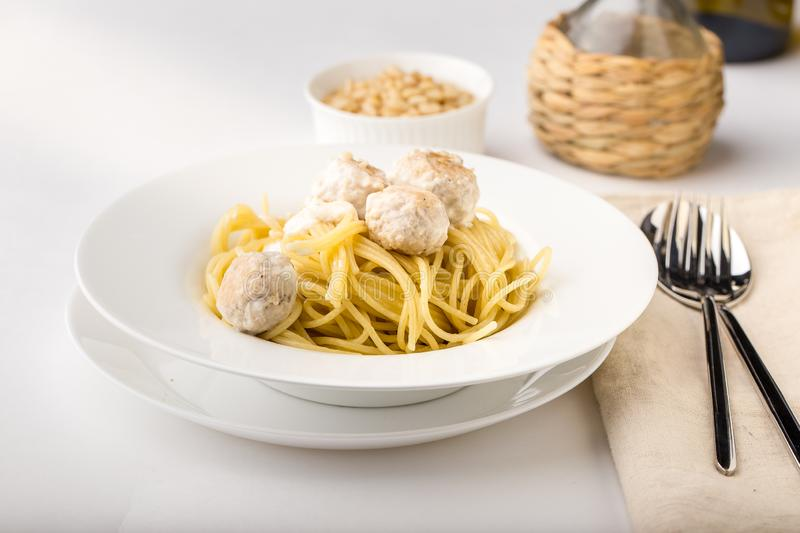 Spaghetti with creamy chicken meatballs served on white plate stock photo