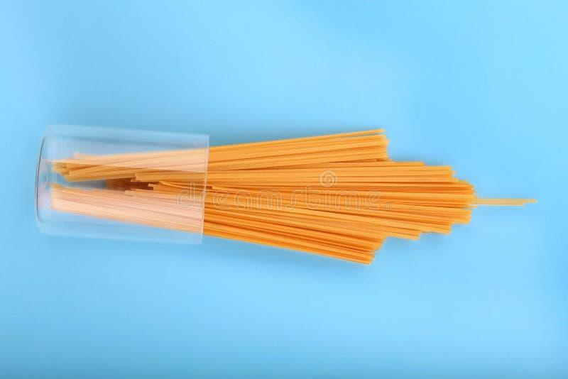 Spaghetti crudi, freschi ed organici su un fondo blu luminoso Pasta e spaghetti asciutti gialli per l'ingrediente di alimento ita fotografia stock