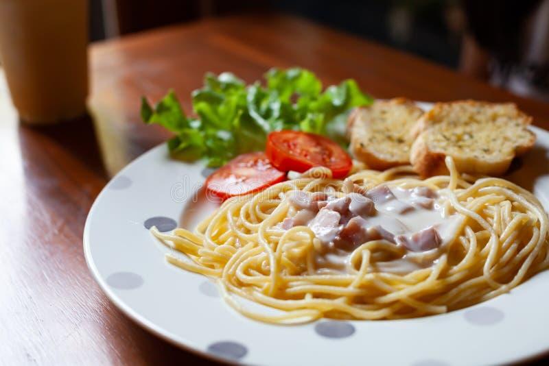 Spaghetti délicieux Carbonara avec du pain à l'ail sur le plat images stock