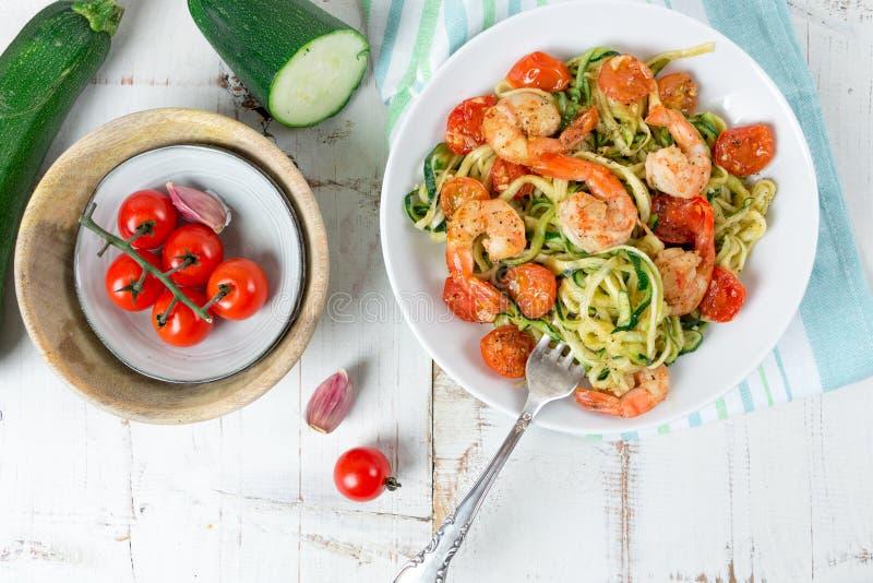 Spaghetti de courgette faits sauter avec la tomate-cerise et les crevettes roses sur le petit morceau photos libres de droits