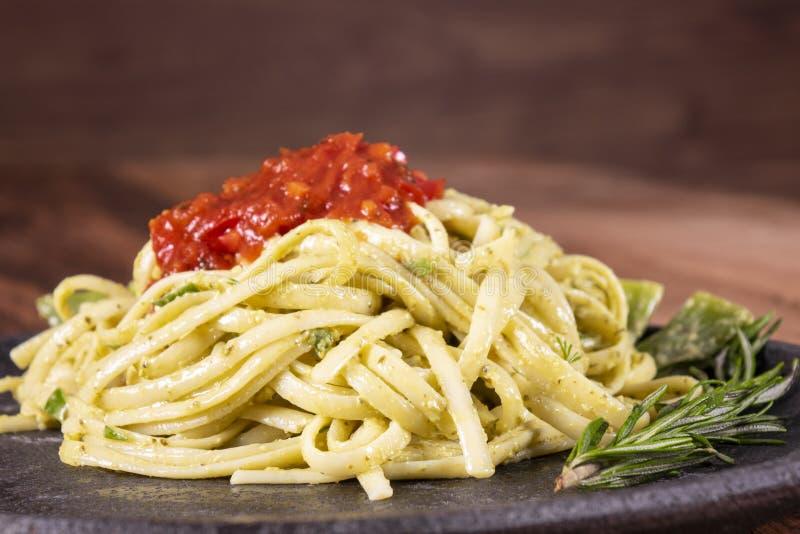 Spaghetti de pâtes avec la courgette, le basilic, la crème et le fromage sur la table en pierre noire photo libre de droits