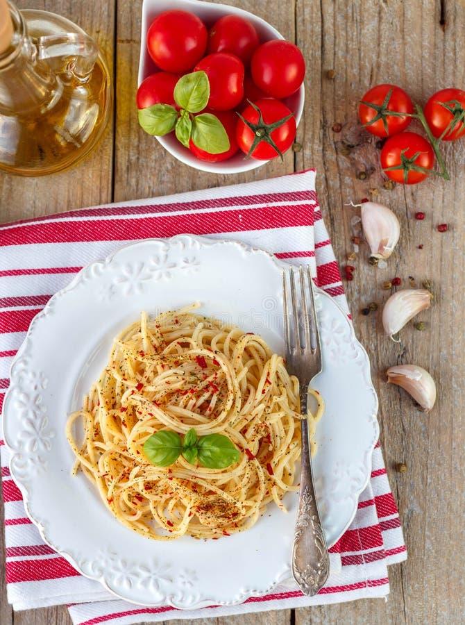 Spaghetti de pâtes avec les tomates et le Basil d'un plat blanc photographie stock libre de droits