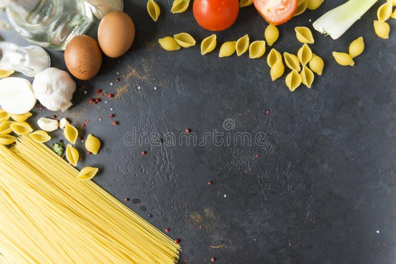 Spaghetti de p?tes et coquilles crus, oeufs, tomate, ?pices, bouteille d'huile sur le fond noir, endroit pour l'inscription photo stock