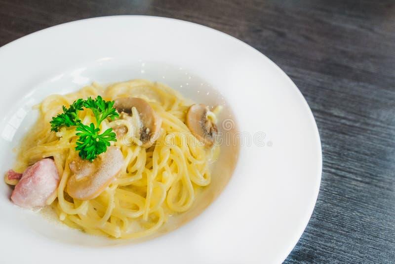 Spaghetti del fungo e del bacon in piatto bianco fotografie stock