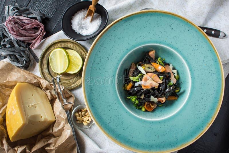 Spaghetti del nero dell'inchiostro della seppia con il salmone e le verdure immagini stock