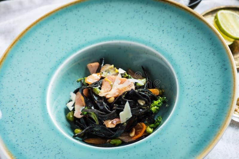 Spaghetti del nero dell'inchiostro della seppia con il salmone e le verdure immagine stock libera da diritti