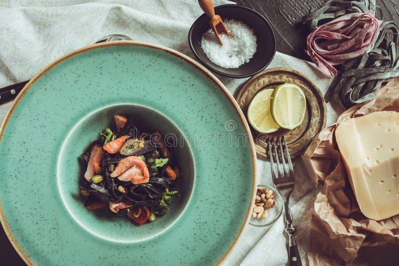 Spaghetti del nero dell'inchiostro della seppia con il salmone e le verdure su Gre immagini stock libere da diritti