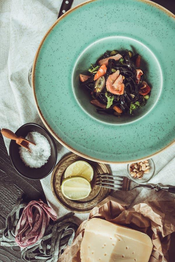 Spaghetti del nero dell'inchiostro della seppia con il salmone e le verdure su Gre immagini stock