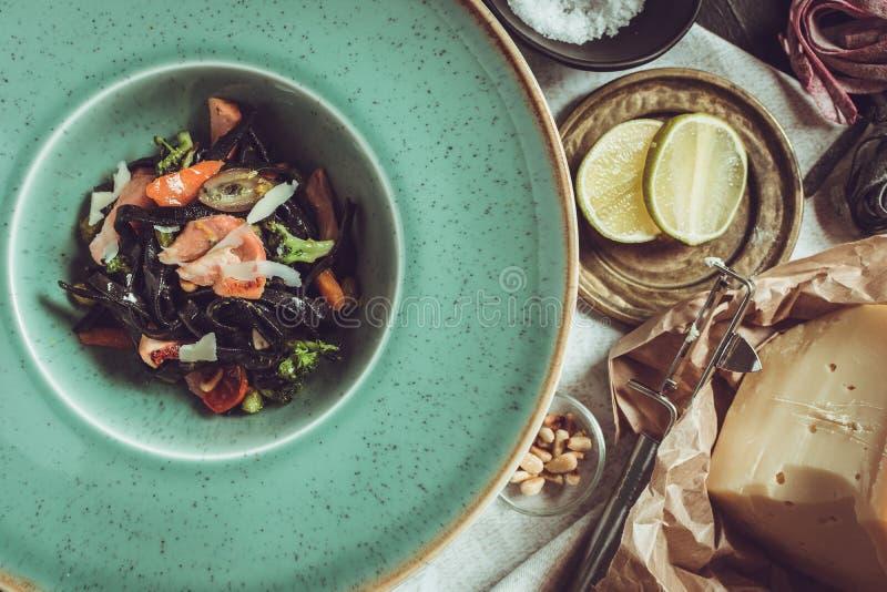 Spaghetti del nero dell'inchiostro della seppia con il salmone e le verdure su Gre fotografia stock libera da diritti