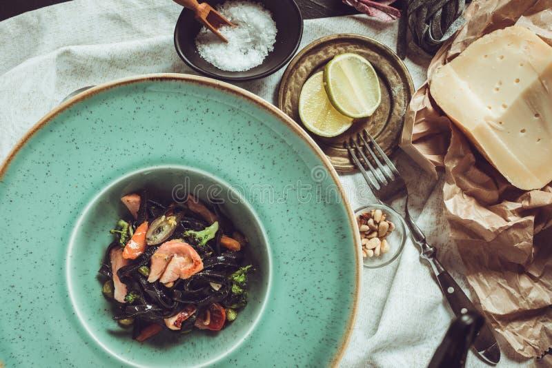 Spaghetti del nero dell'inchiostro della seppia con il salmone e le verdure su Gre fotografie stock libere da diritti
