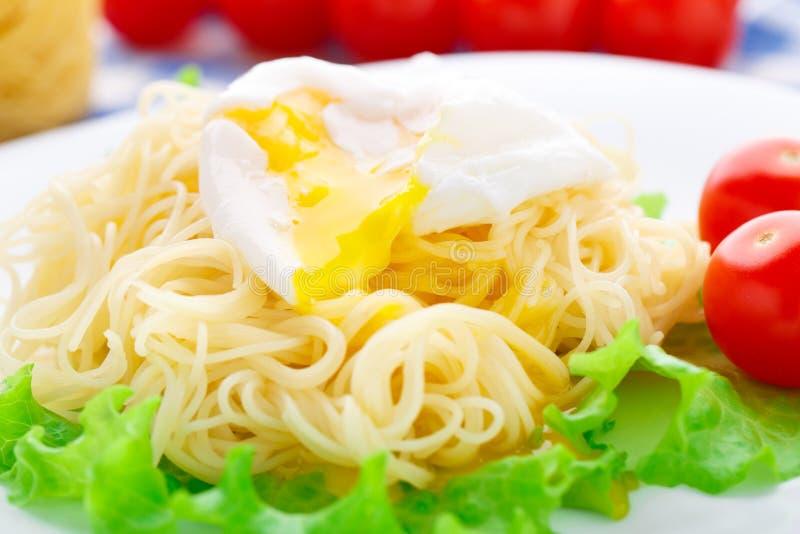 Spaghetti deliziosi con il pomodoro e l'uovo affogato fotografia stock