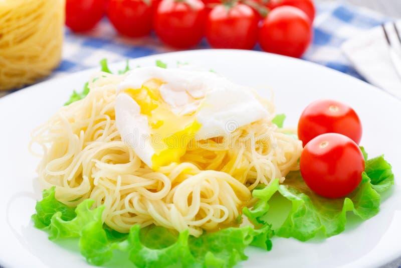 Spaghetti deliziosi con il pomodoro e l'uovo affogato fotografie stock libere da diritti