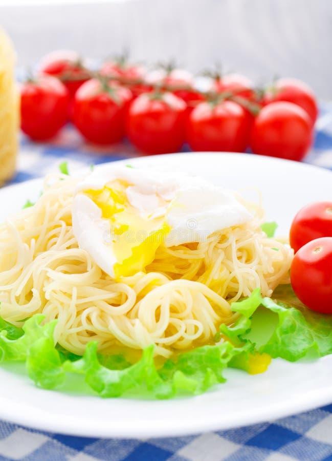 Spaghetti deliziosi con il pomodoro e l'uovo affogato immagini stock libere da diritti