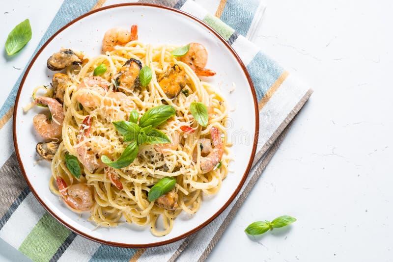 Spaghetti della pasta con frutti di mare e salsa crema su bianco immagini stock