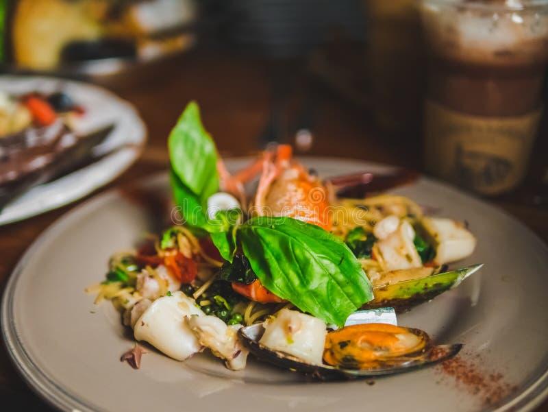 Spaghetti della pasta dei frutti di mare deliziosi con le vongole, gamberetti, cappasante americane piccanti sulla tavola di legn immagini stock