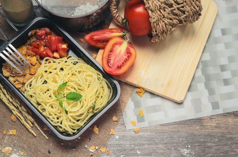 Spaghetti die in een kleine rode ijzerpan met tomaten en korrels wordt voorbereid die smakelijk kijken royalty-vrije stock foto