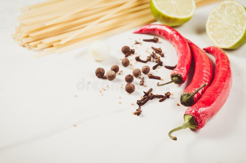 spaghetti e condimenti per la preparazione/gli spaghetti e condimenti per la preparazione su un fondo bianco Copi lo spazio immagine stock