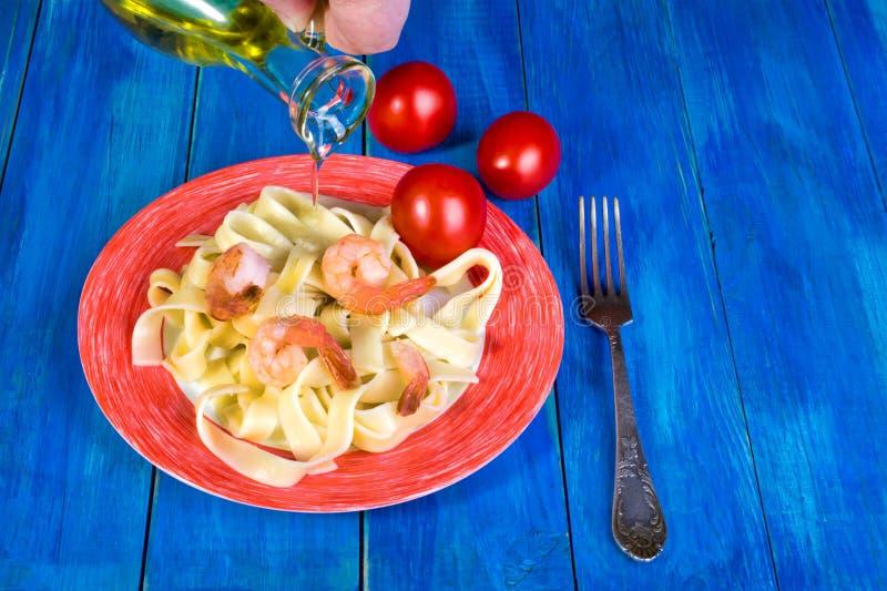 Spaghetti e gamberetto in un piatto bianco con un confine rosso e rosso immagini stock