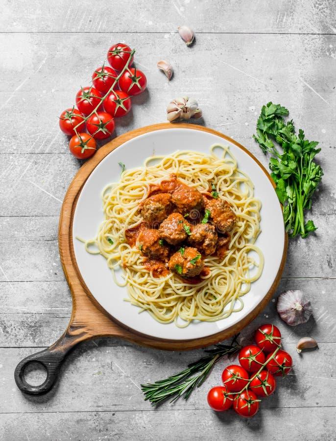 Spaghetti e polpette su una piastrina con i pomodori, le erbe e l'aglio immagini stock libere da diritti