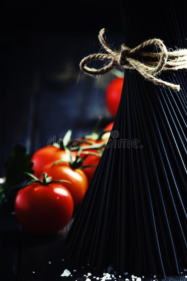 Spaghetti e pomodori, natura morta nel fuoco scuro e selettivo fotografia stock libera da diritti