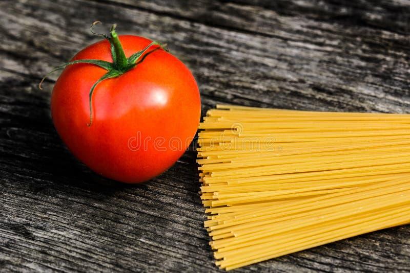 Spaghetti e pomodoro su un banco di legno rustico fotografia stock